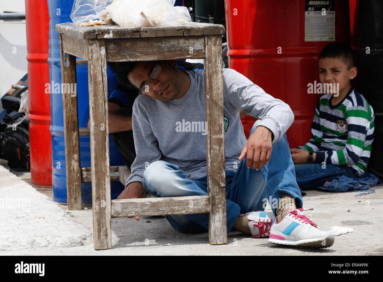Los migrantes están buscando sombra mientras espera para ir al campamento. Hundrends migrantes llegó cada Imagen De Stock