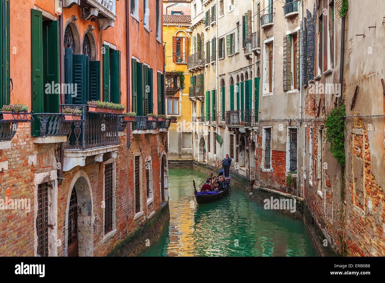 Góndola por canal pequeño entre las viejas casas en Venecia, Italia. Imagen De Stock
