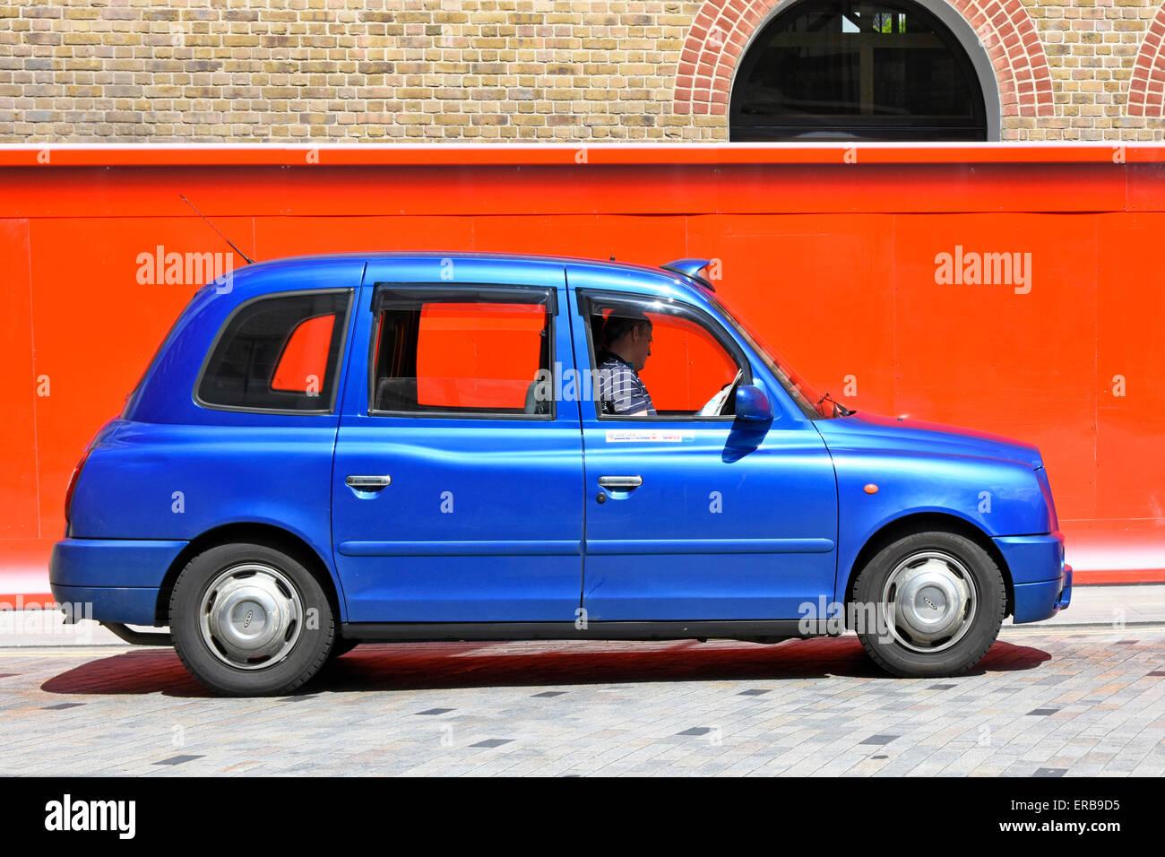 Londres taxi driver lee su papel, mientras que la cola para los clientes en la estación Kings Cross Camden Imagen De Stock