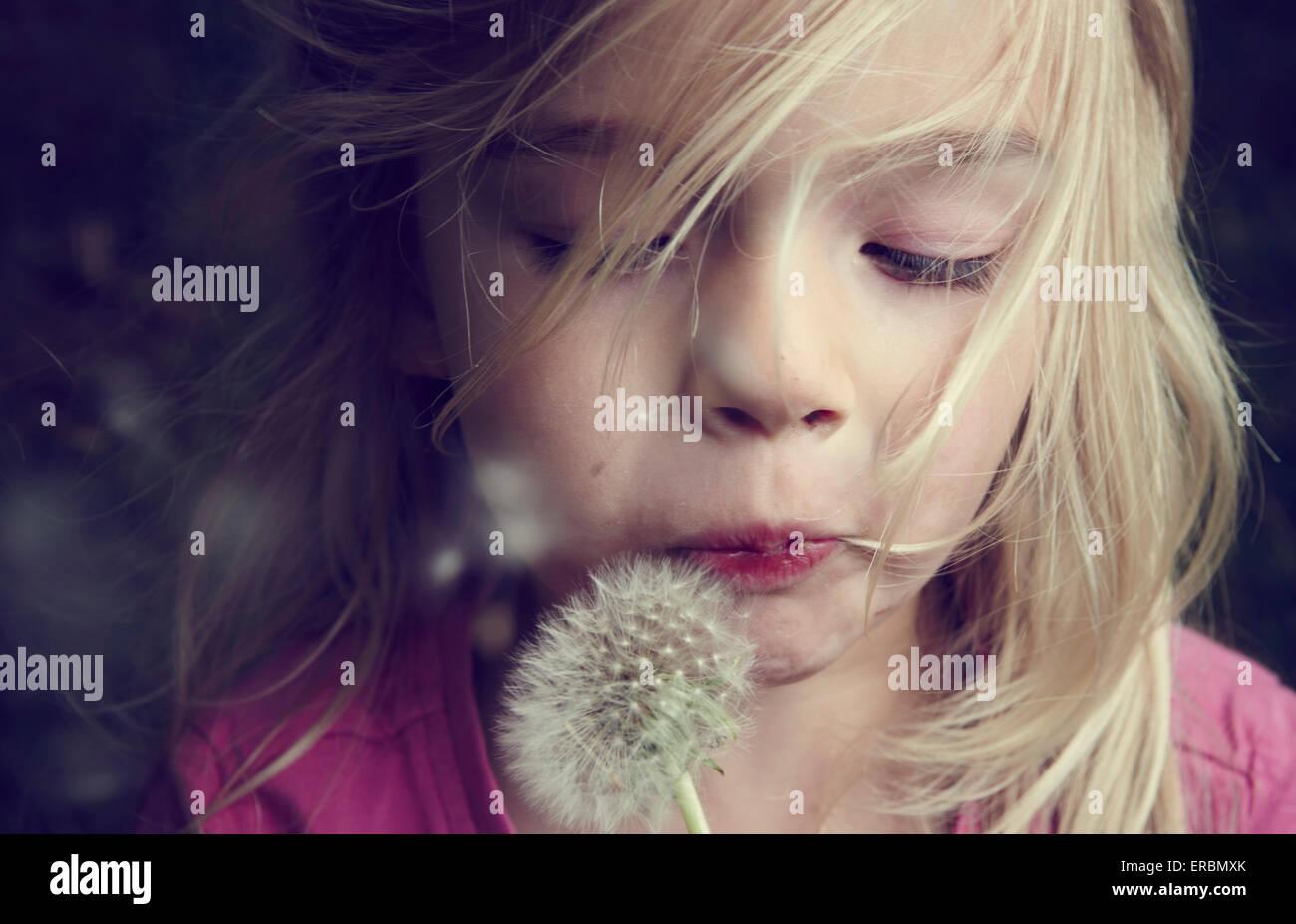 Retrato de chica rubia caucásica soplando flor semillas de diente de león Imagen De Stock
