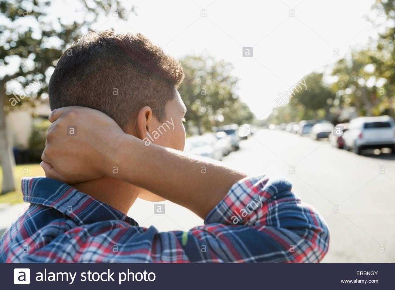 Joven mirando hacia abajo de la calle soleada Imagen De Stock