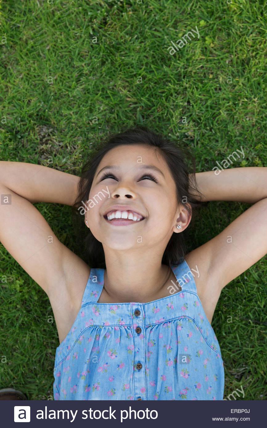 Chica sonriente tendido en la hierba de las manos detrás de la cabeza Foto de stock