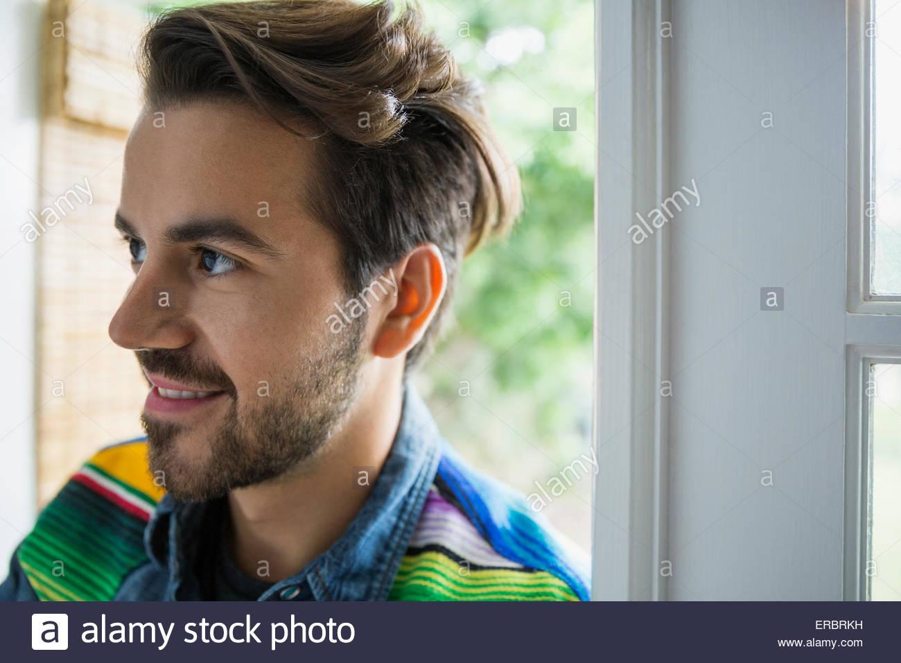 Morena sonriente hombre en el umbral mirando lejos Imagen De Stock