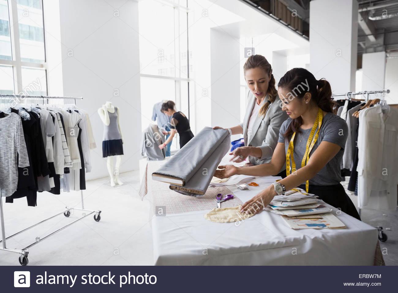 Los diseñadores de moda trabajan con tejidos y patrones de costura Imagen De Stock