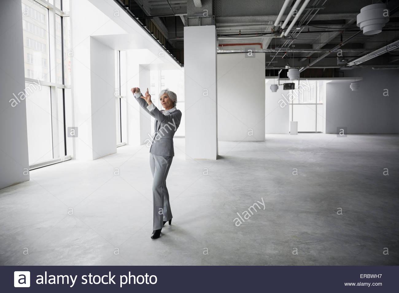 La empresaria con dedos de ideación fotograma en oficina vacía Imagen De Stock