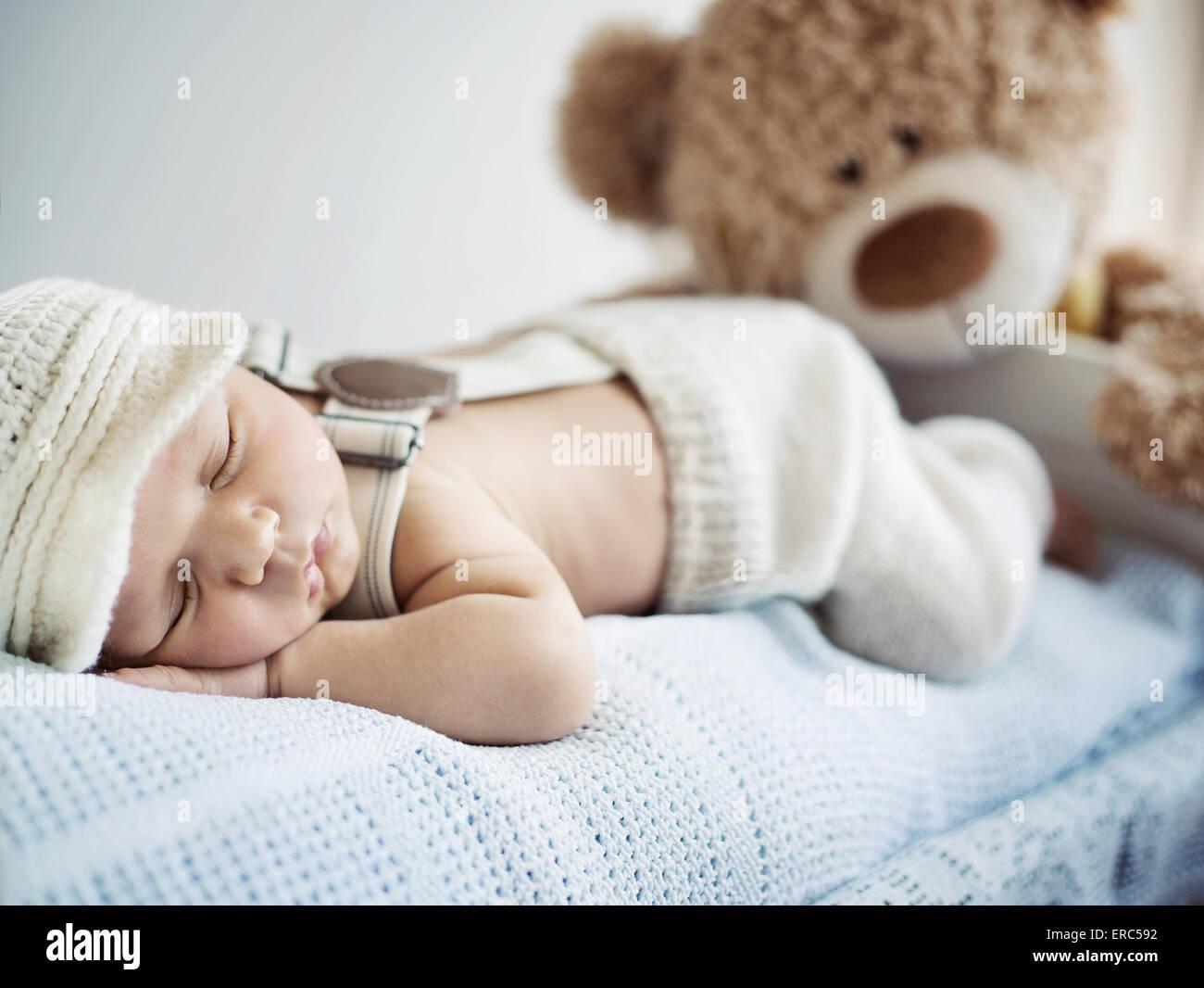 Niño recién nacido duerme con un oso de peluche Foto de stock