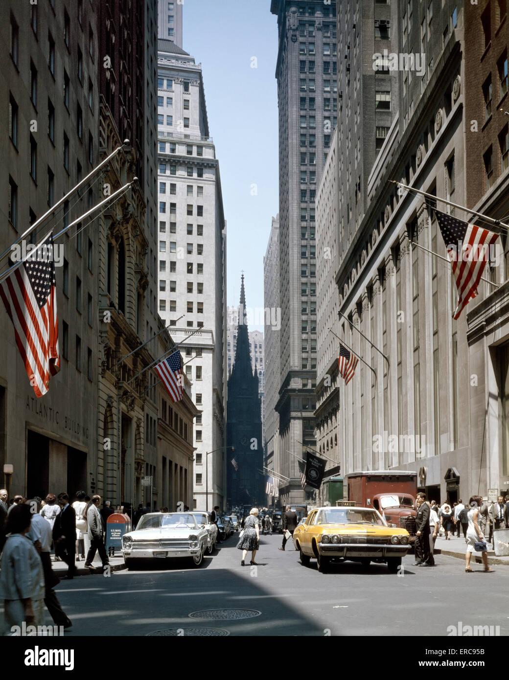 1960 vista abajo WALL STREET a la Trinity Church en el centro de Manhattan, Nueva York, EE.UU. Imagen De Stock