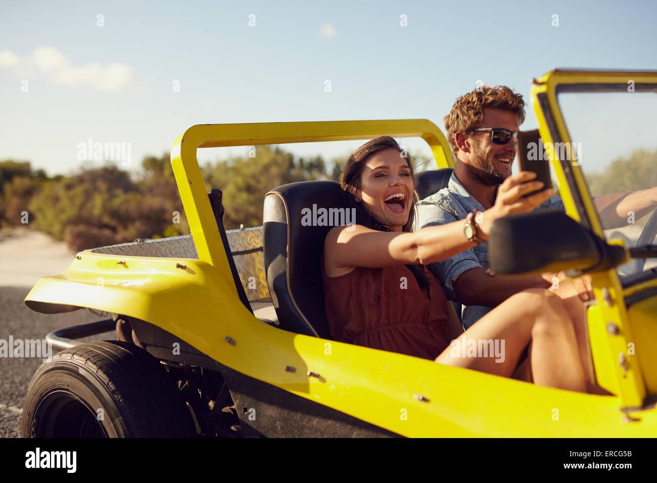 Emocionada feliz pareja disfrutando de viaje por carretera en su coche. El hombre conducía el coche joven teniendo Imagen De Stock