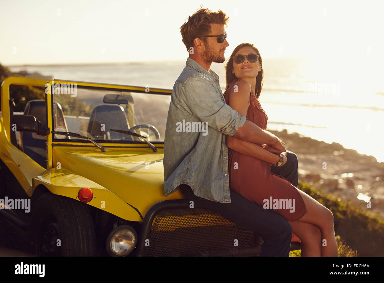 Retrato de la romántica pareja joven sentado sobre el capó de su coche con el hombre abrazando a la mujer Imagen De Stock