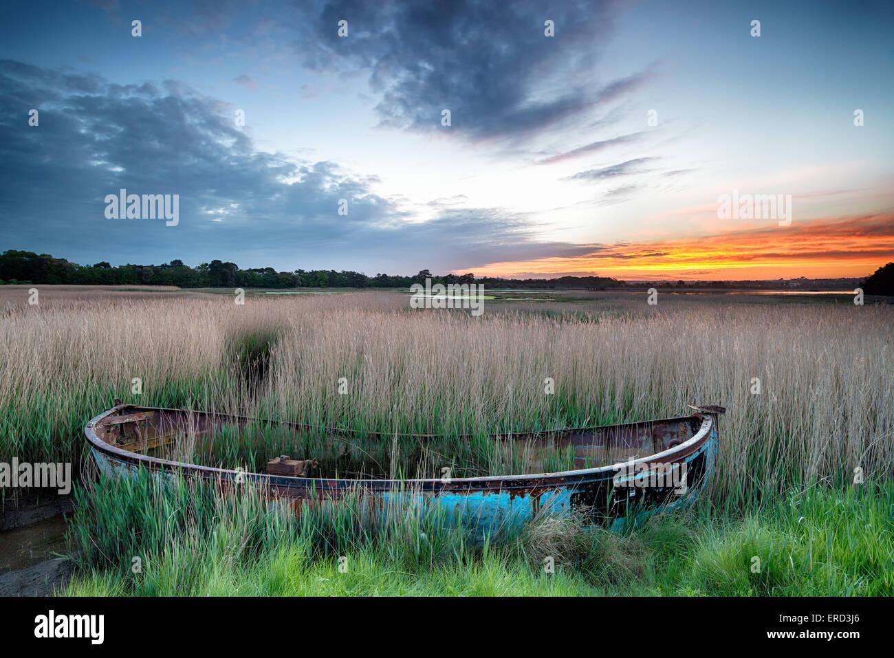 Amanecer sobre un viejo barco pesquero se lavan en juncos en Poole Harbour en la costa de Dorset Imagen De Stock