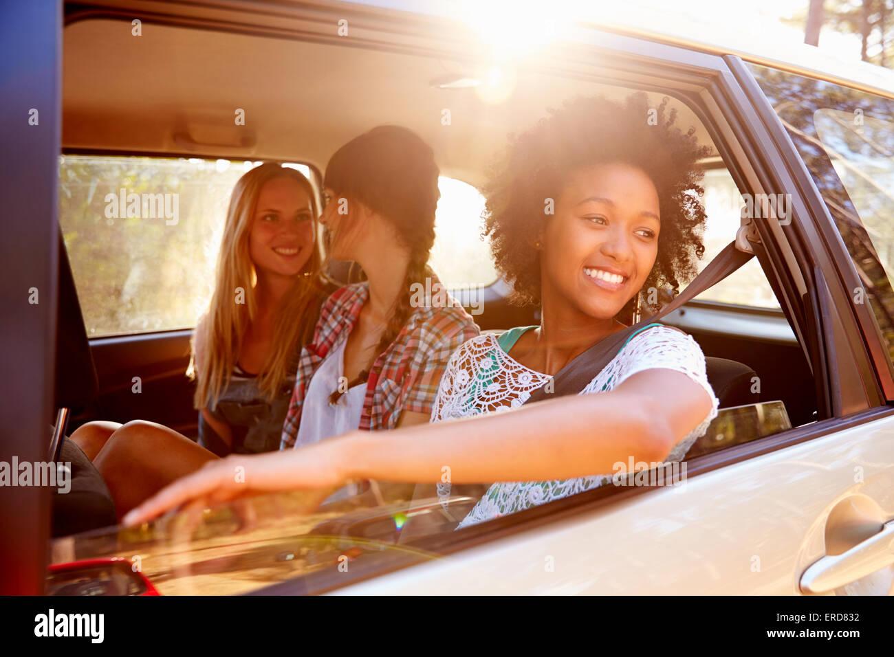 Tres mujeres sentadas en el asiento trasero del coche en Road Trip. Imagen De Stock