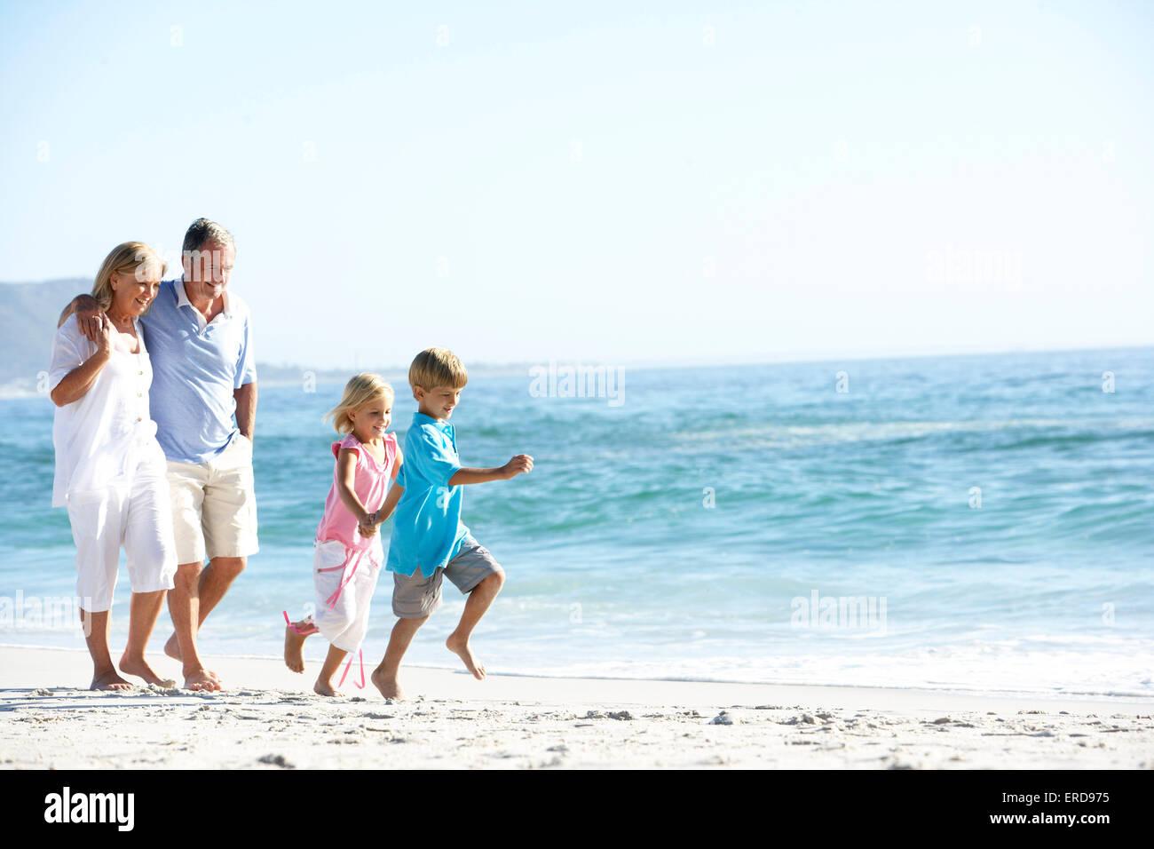 Abuelos y nietos caminando por la playa Foto de stock