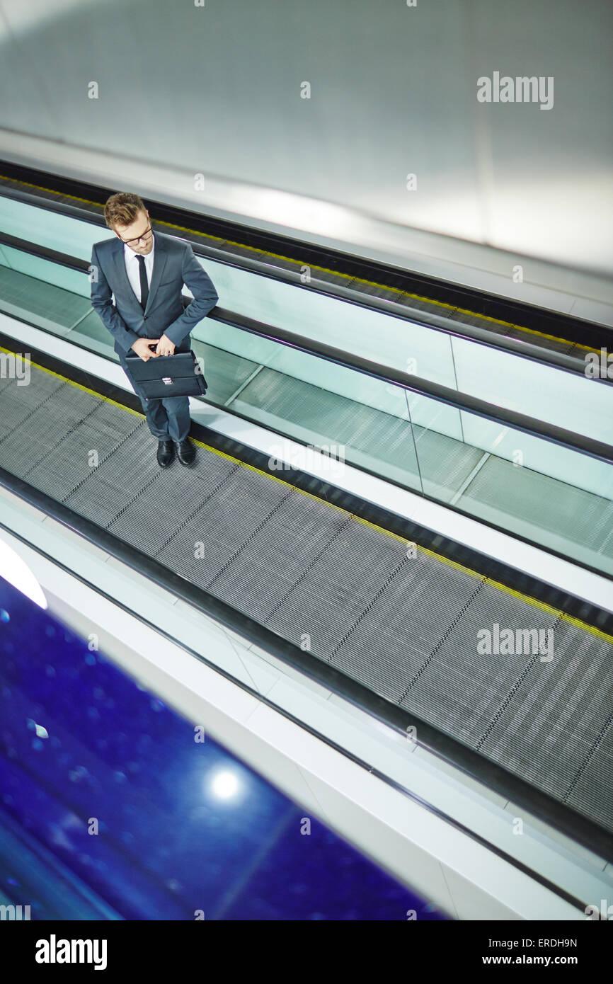 Empresario con elegante maletín moviendo hacia arriba en la escalera mecánica Imagen De Stock
