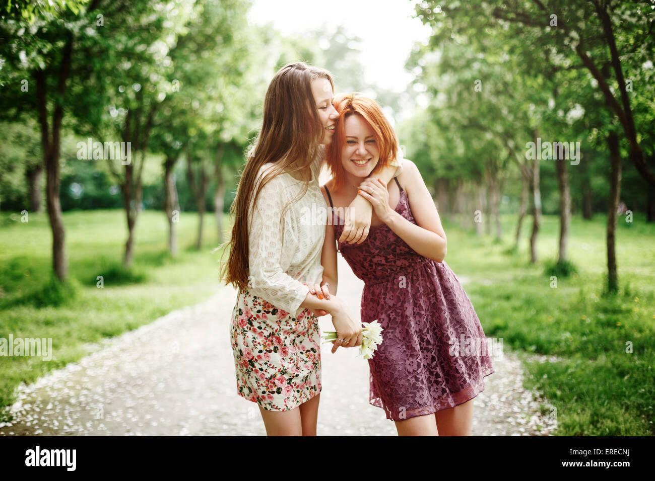 Dos jóvenes felices chicas que se divierten en el parque de verano. Mejores amigos riendo y abrazando. Imagen De Stock