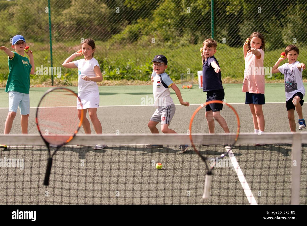 Niños jugando juegos de tenis en un evento de caridad de tenis, Headley, Hampshire, Reino Unido. Imagen De Stock