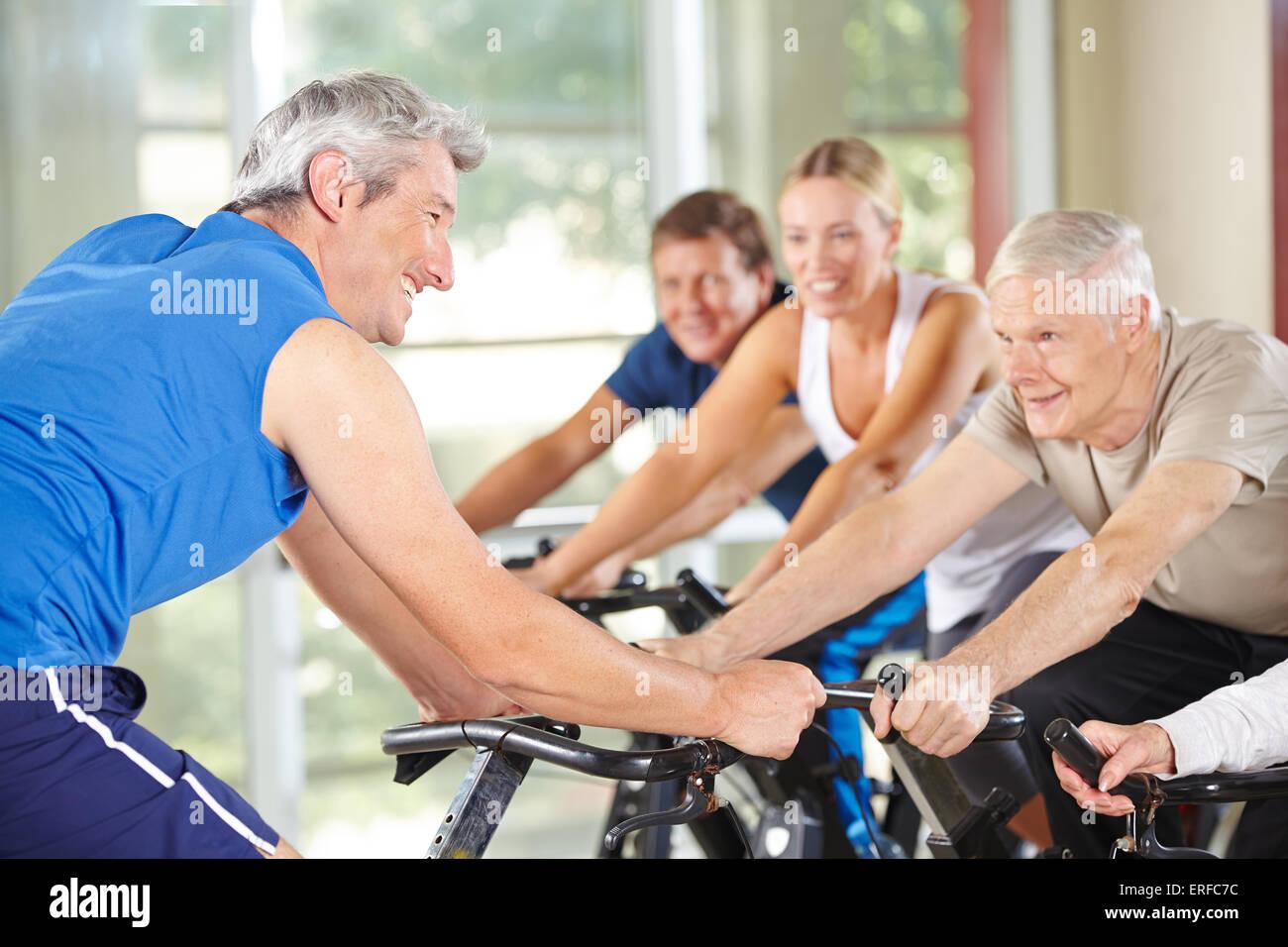 Las personas de mayor rango en la clase de spinning en un gimnasio con entrenador Imagen De Stock