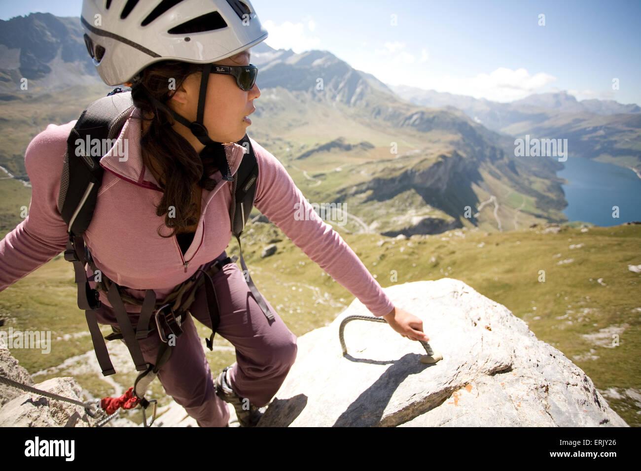 Una joven toma un momento para disfrutar del paisaje mientras practica el deporte de Vía ferrata en los Alpes Imagen De Stock