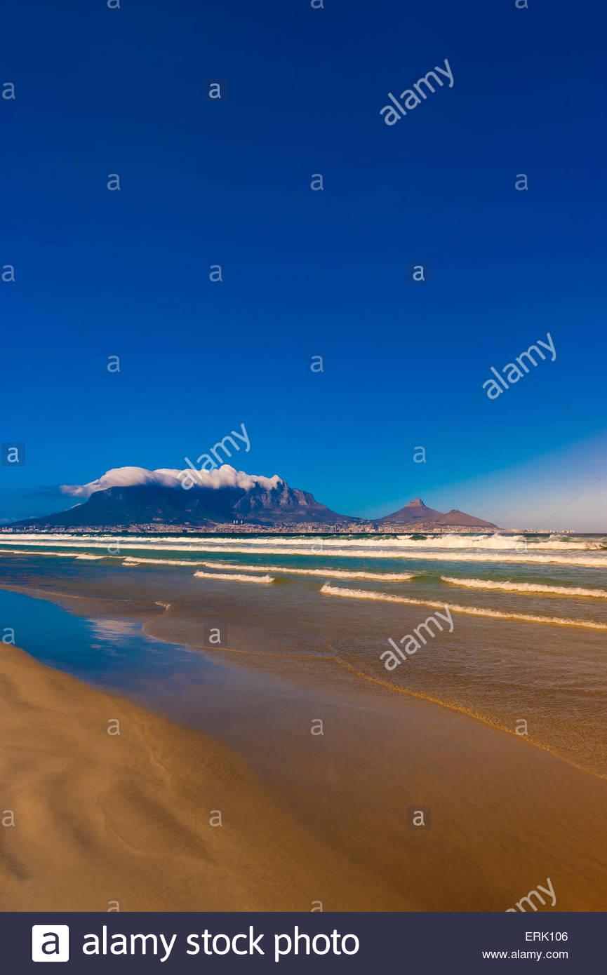 Vista de Ciudad del Cabo y Table Mountain y el pico de cabeza de león en la playa en Milnerton, Sudáfrica. Imagen De Stock