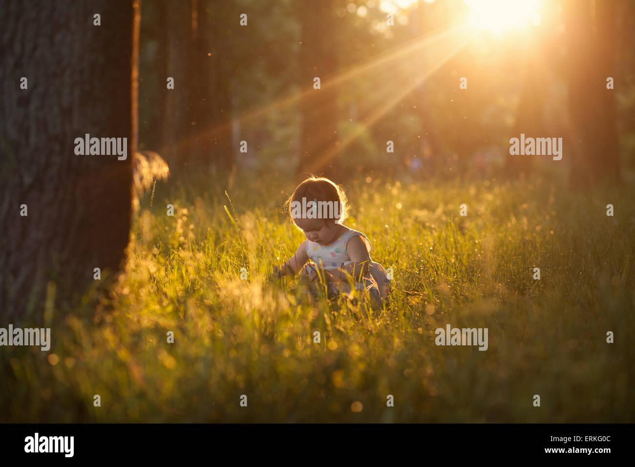 Hermosa toma de jugar al bebé en luces al atardecer Imagen De Stock