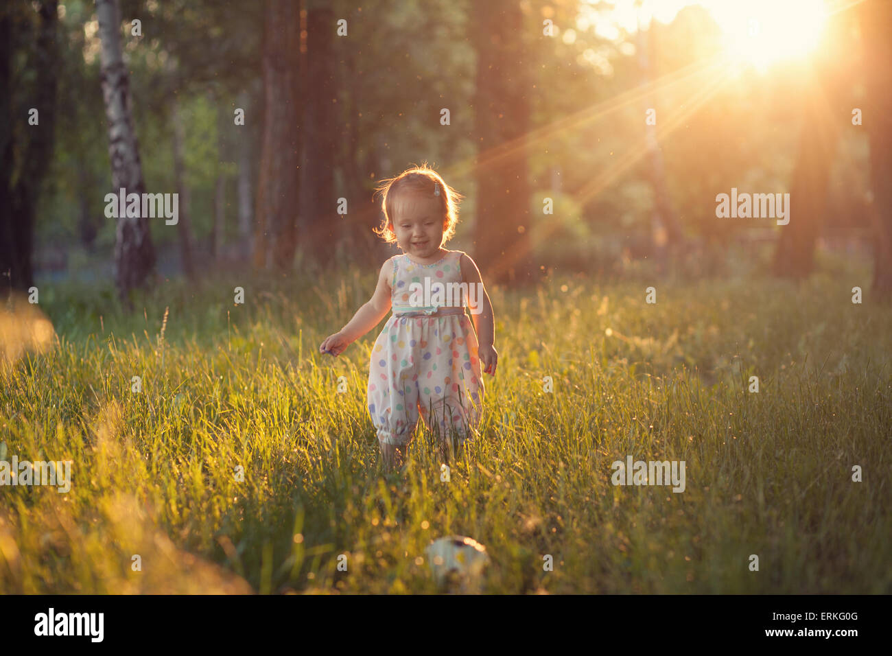 Bebé jugando en luces al atardecer Imagen De Stock