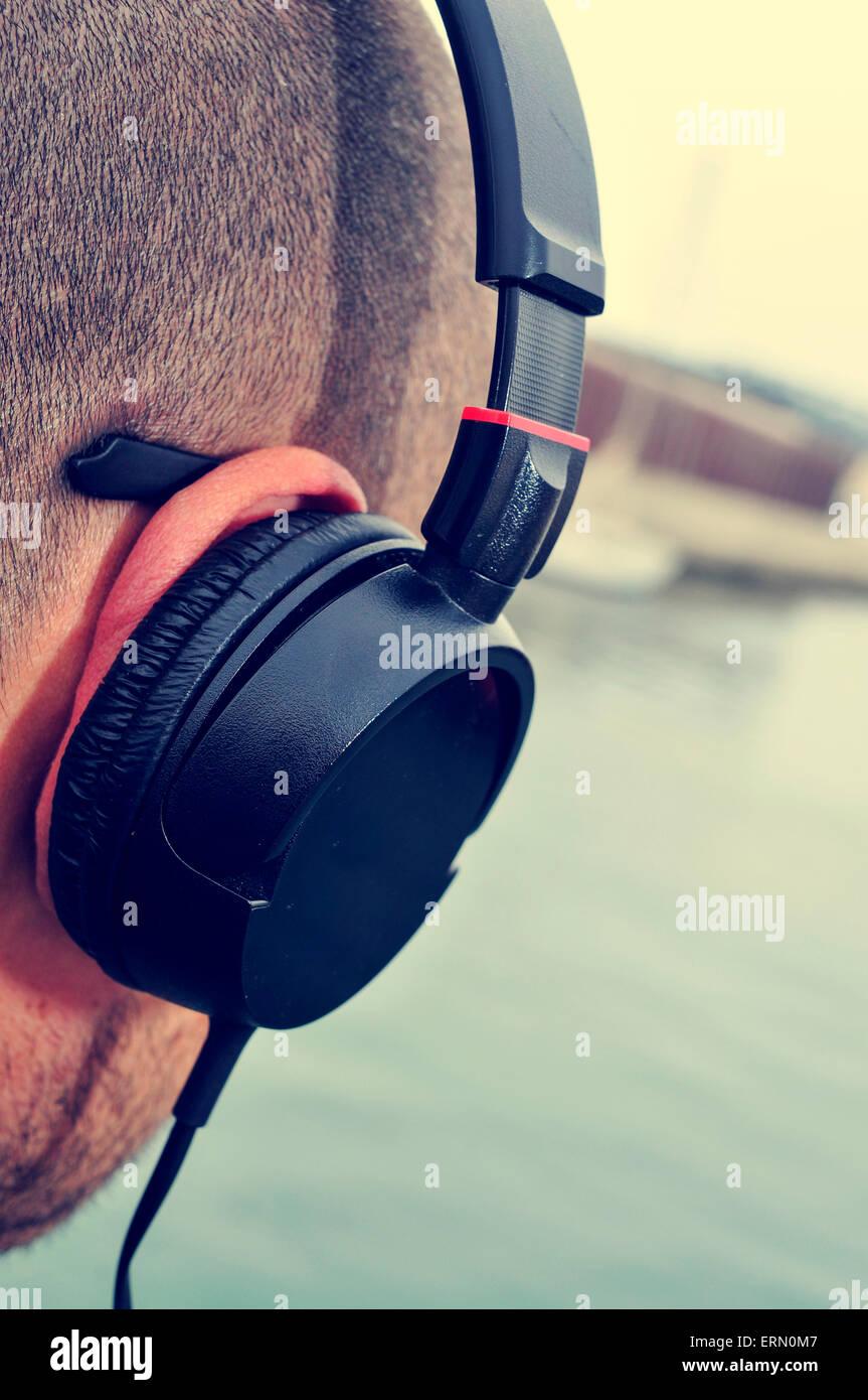 Primer plano de un joven hombre caucásico escuchar música con auriculares en la parte frontal del mar Imagen De Stock