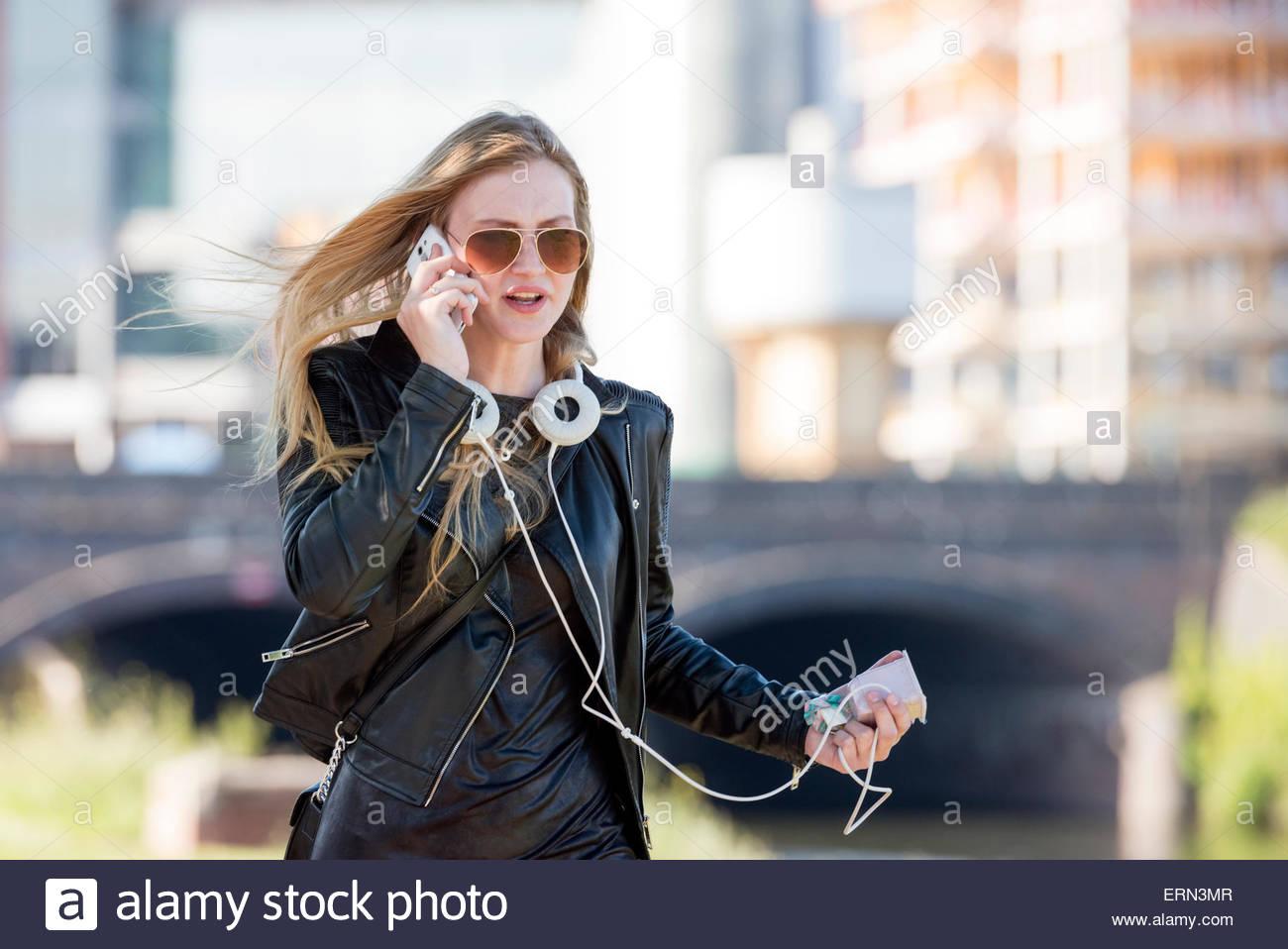 Joven Mujer rubia hablando por un teléfono móvil mientras camina por la calle en Cardiff, Gales, Reino Imagen De Stock
