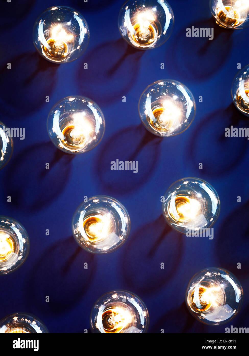 Un grupo de bombillas de luz incandescente iluminada brilla sobre fondo azul. Imagen De Stock