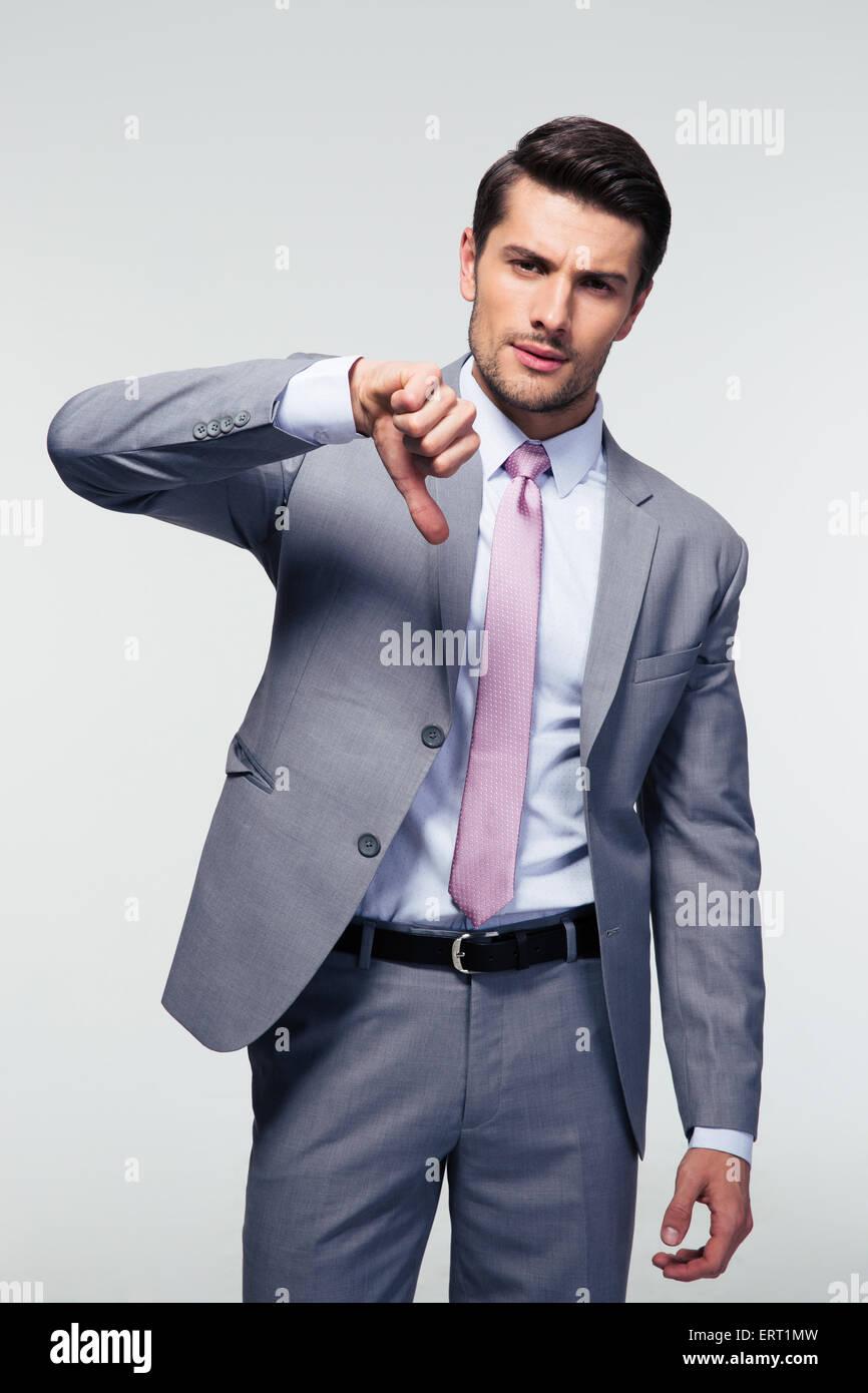 Seguros de empresario mostrando pulgar abajo señal sobre fondo gris. Mirando a la cámara Imagen De Stock