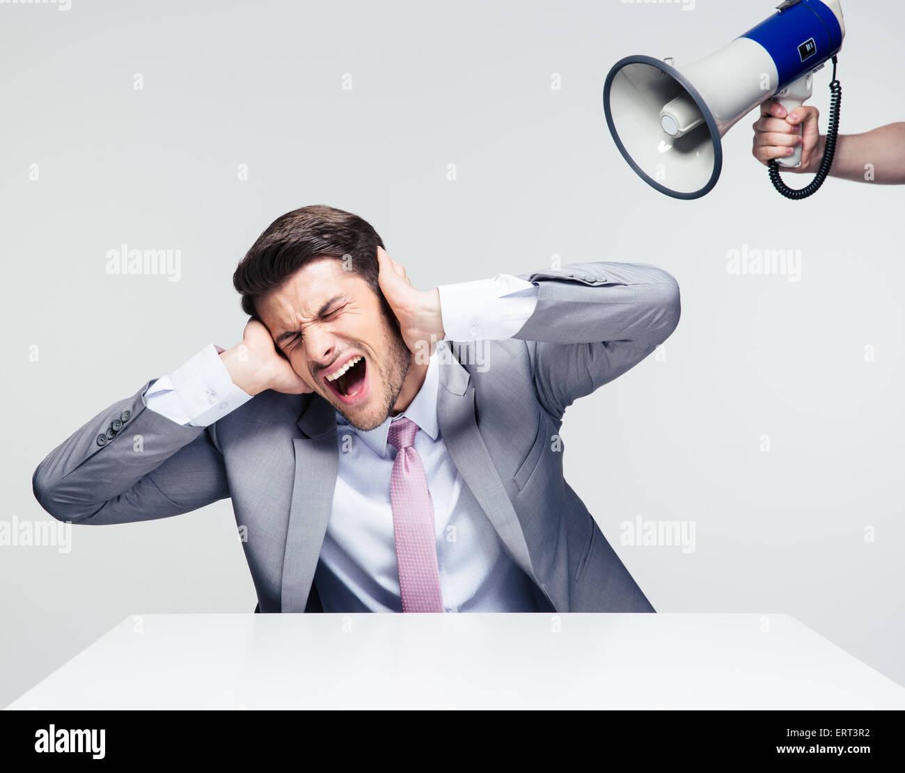 Empresario sentado en la mesa y cubriendo sus oídos de megáfono sobre fondo gris Imagen De Stock