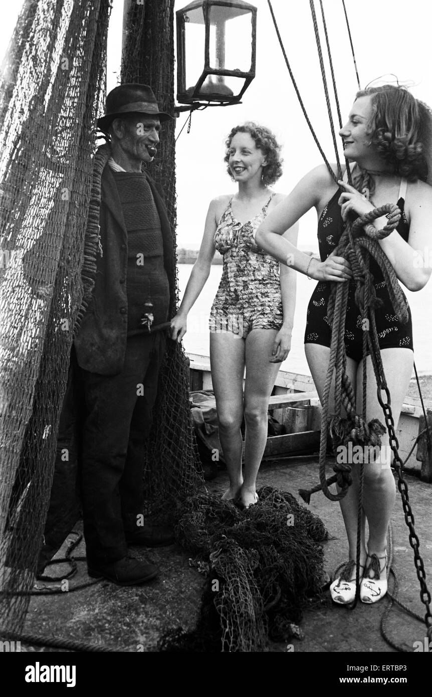 5249ac6fe3f8 Las mujeres en sus trajes de baño con un pescador, a lo largo de la ...