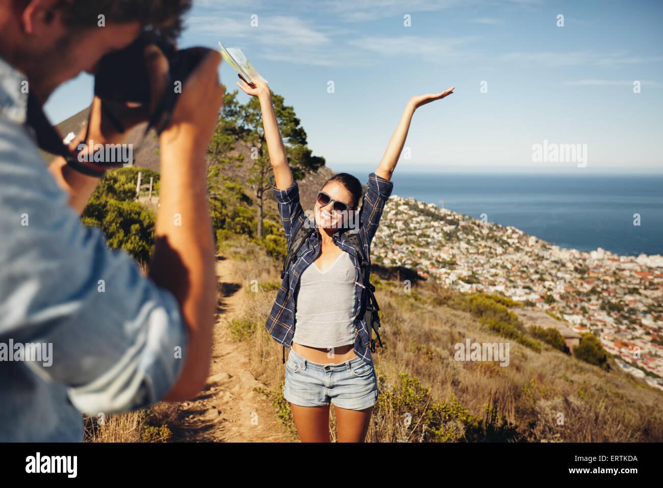 Feliz joven posando con sus brazos levantados a su novio, tomando fotos con su cámara digital. Vacaciones de Imagen De Stock