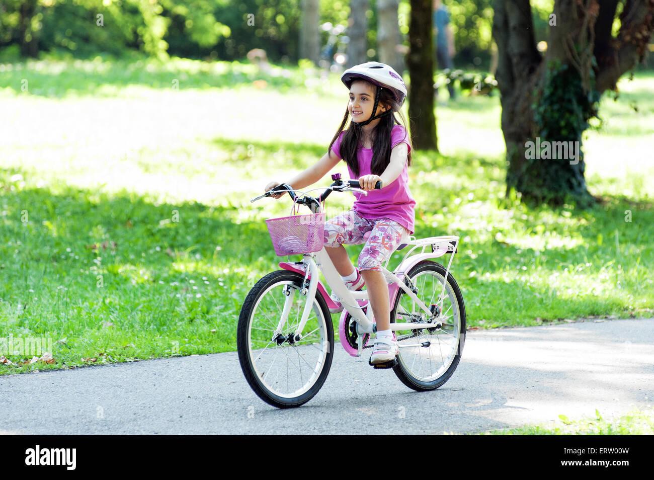 Niña en un moderno traje rosa rosa coincidente con bicicleta y casco montando su bicicleta Imagen De Stock