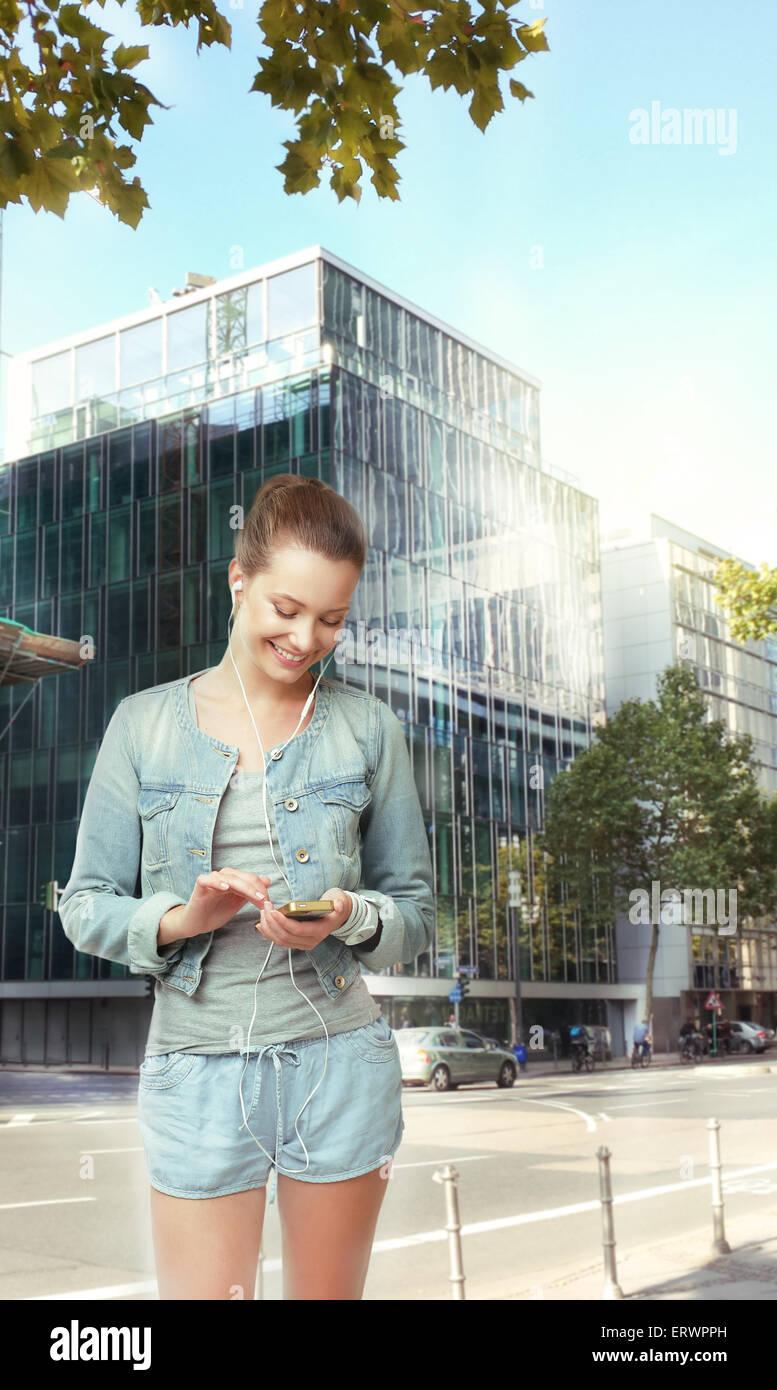 Mujer sonriente con auriculares en la calle Imagen De Stock