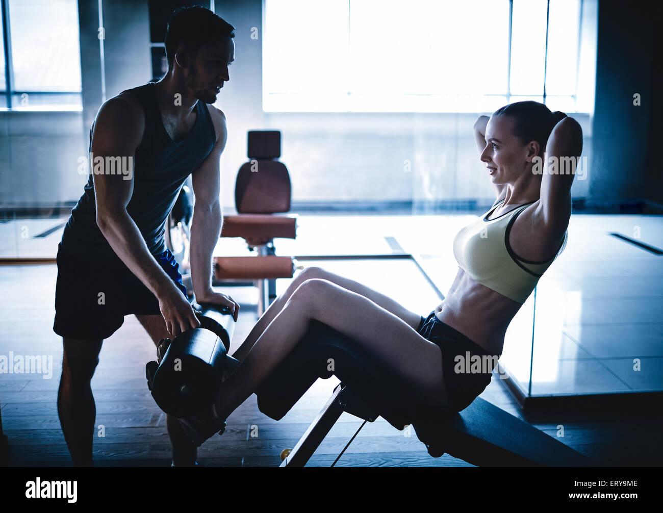 Mujer activa haciendo flexiones en el gimnasio mientras ayudaba a su formador Imagen De Stock