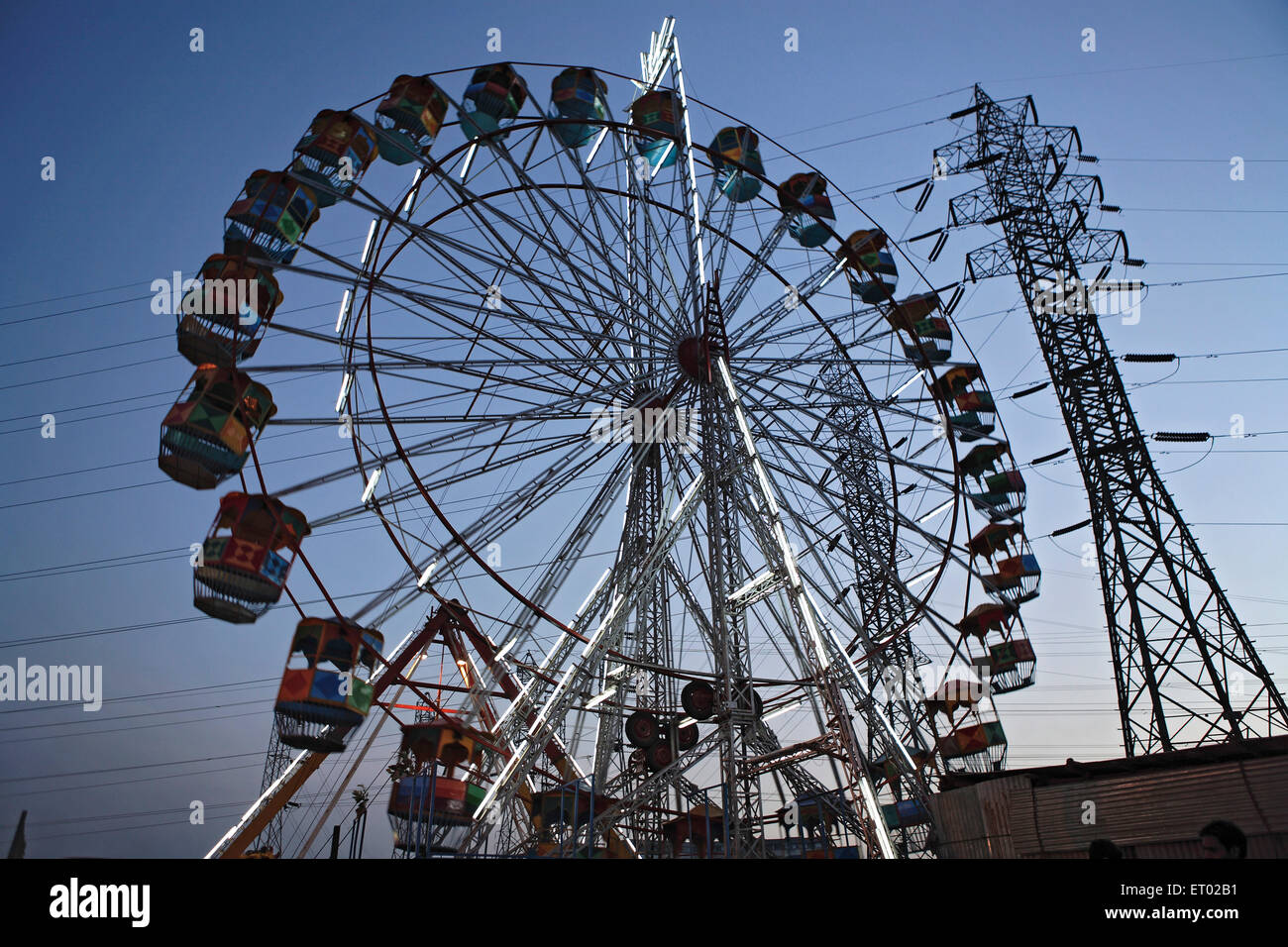 Rueda Gigante en la feria con la torre de transmisión de electricidad en el fondo Foto de stock