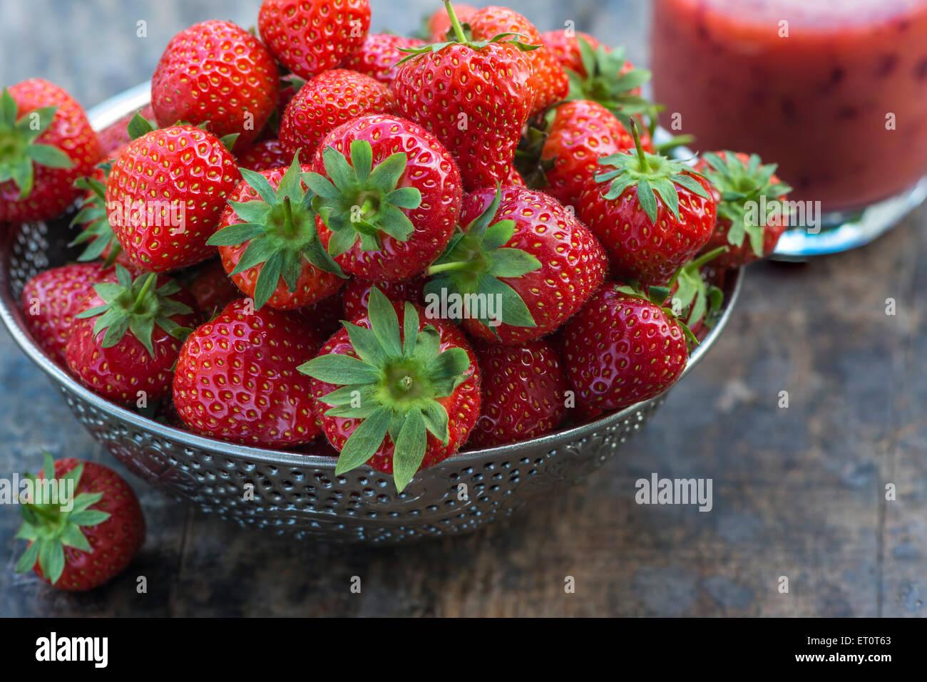 Fresas frescas en un recipiente sobre la mesa de madera Imagen De Stock