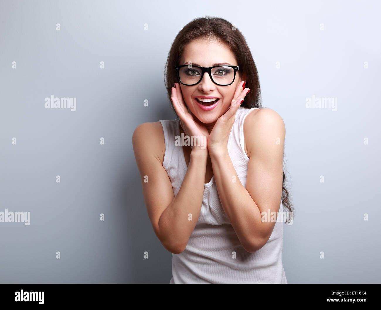 Emocionada sorprendente divertido joven con gafas en la boca abierta sobre fondo azul, con copia espacio vacío Imagen De Stock