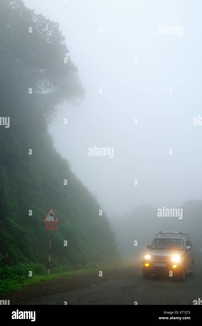 Los faros del vehículo en ambiente neblinoso Mahabaleshwar ; ; ; Maharashtra India el 13 de septiembre de 2009 Imagen De Stock