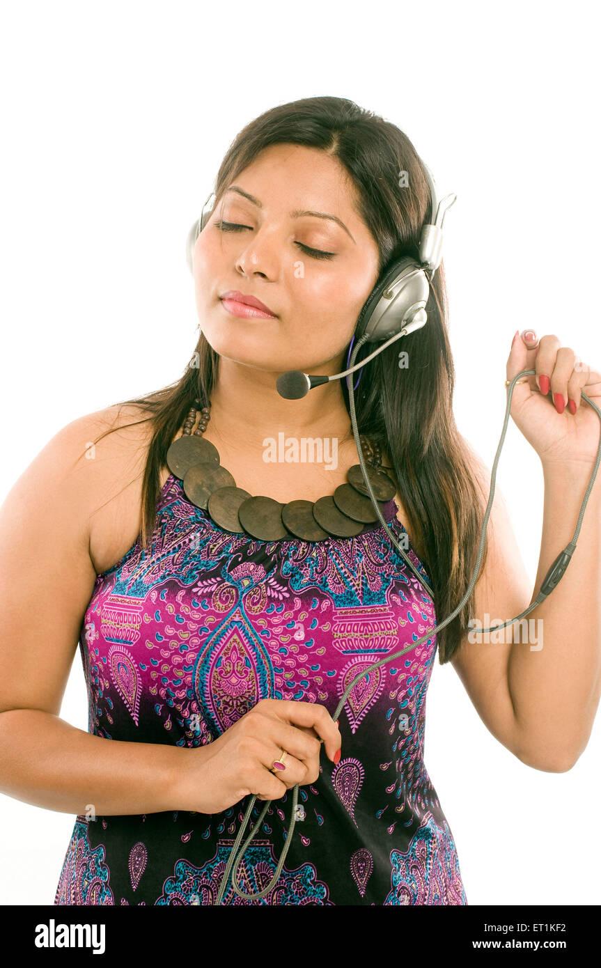 Vestida del sur de la India sin mangas y escuchar música en Pune, en Maharashtra, India Asia MR#686X Imagen De Stock