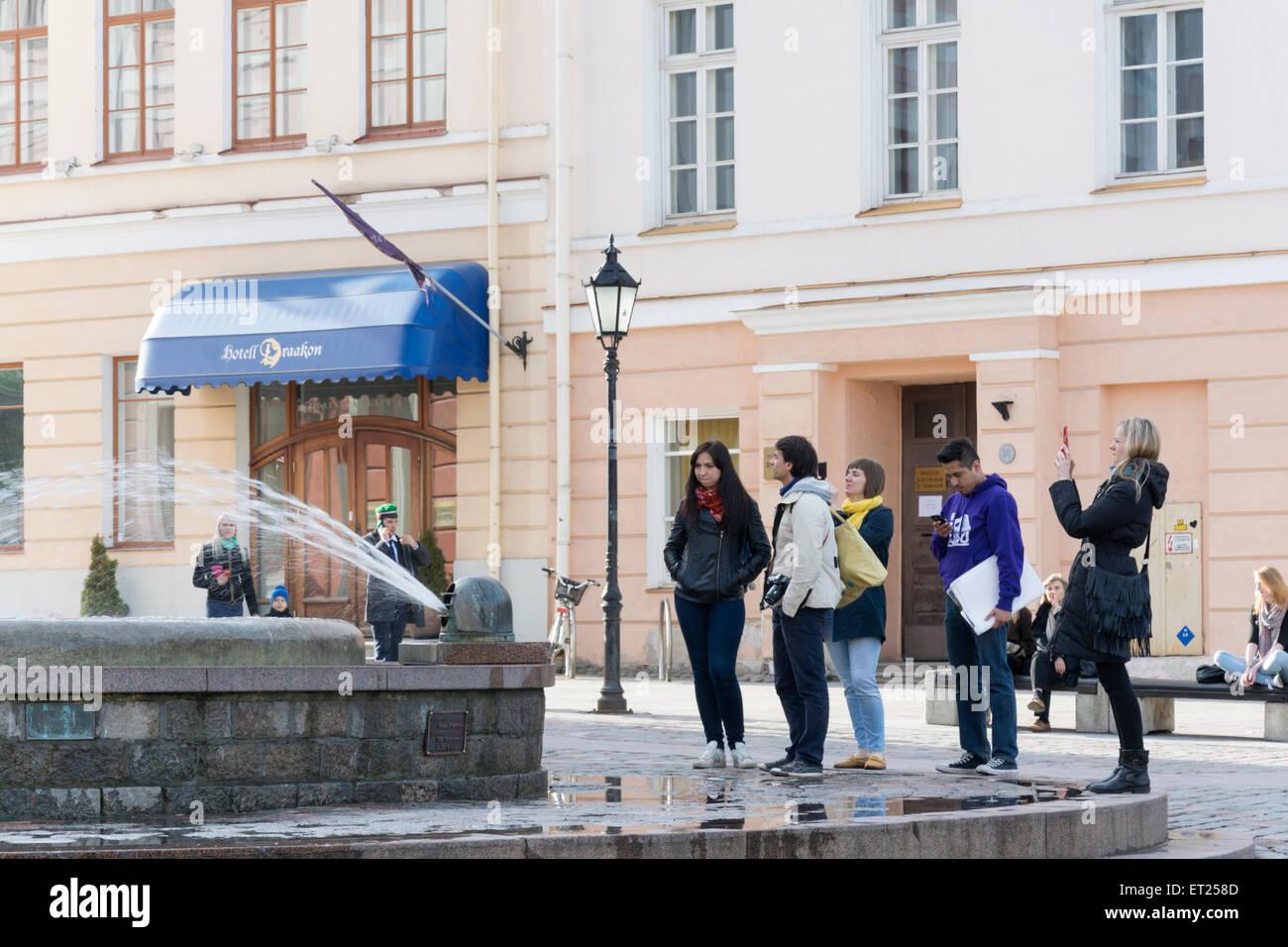 Un grupo de turistas, prestando atención a una fuente en Tartu Estonia Imagen De Stock