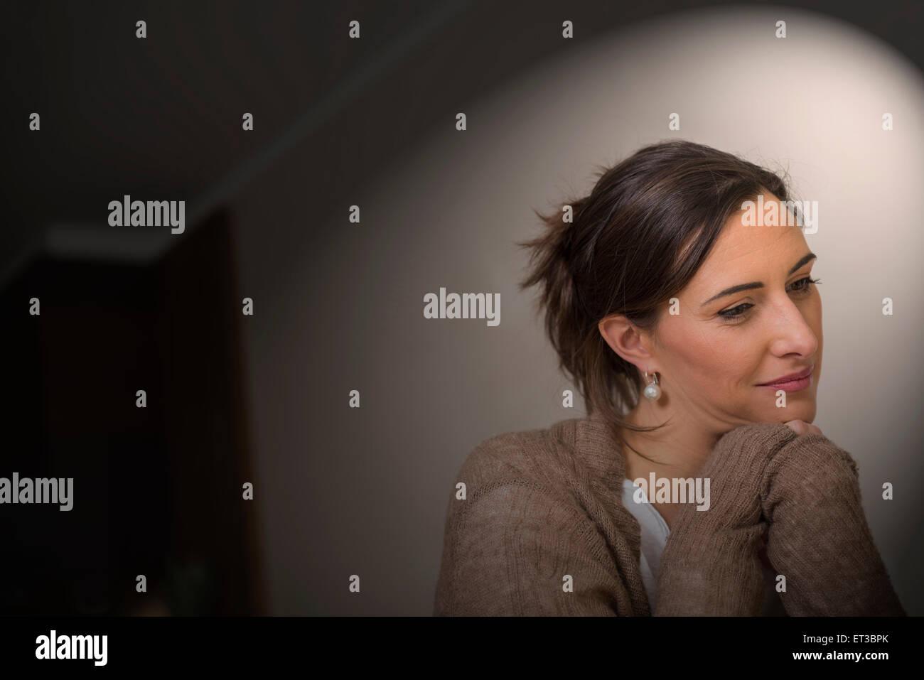 Cerca de una mitad mujer adulta pensando con inclinarse sobre los codos, Munich, Baviera, Alemania Imagen De Stock