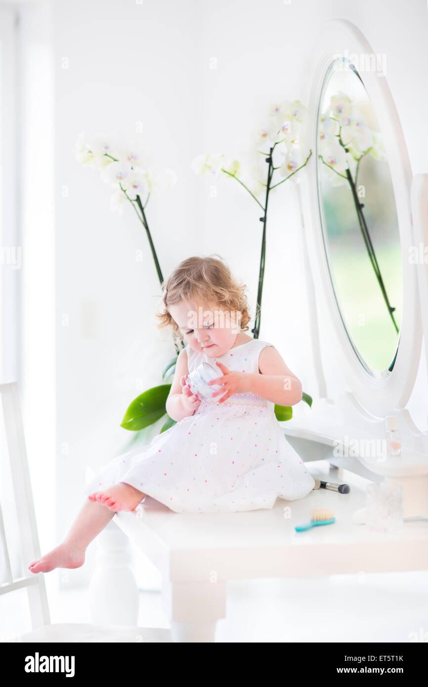 Niño feliz chica con pelo rizado vistiendo un vestido blanco jugando con maquillaje y cosméticos delante Imagen De Stock