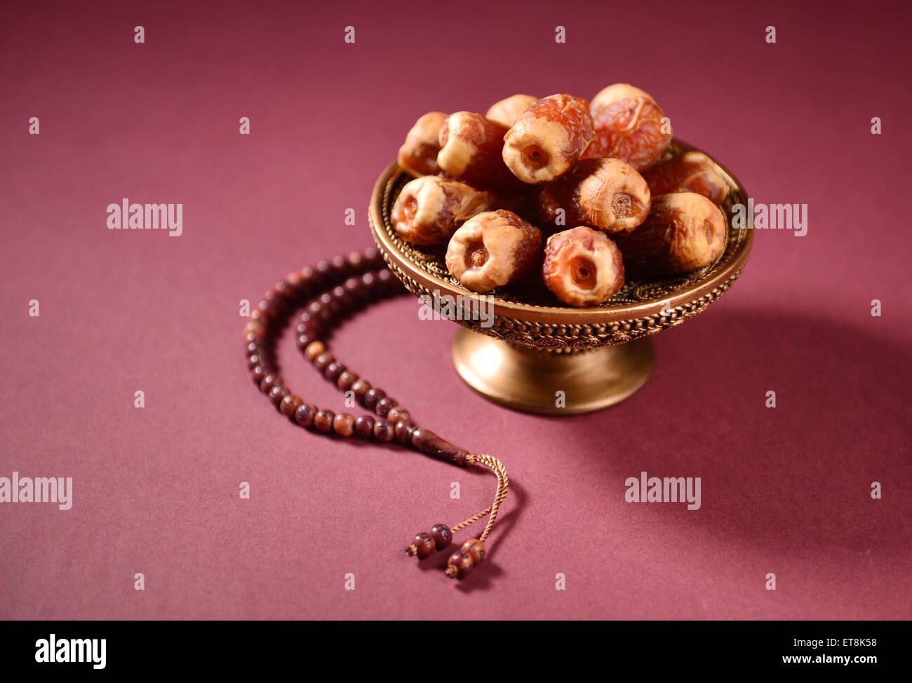 Fechas en un tazón y cordones de oración islámica. Foto de stock
