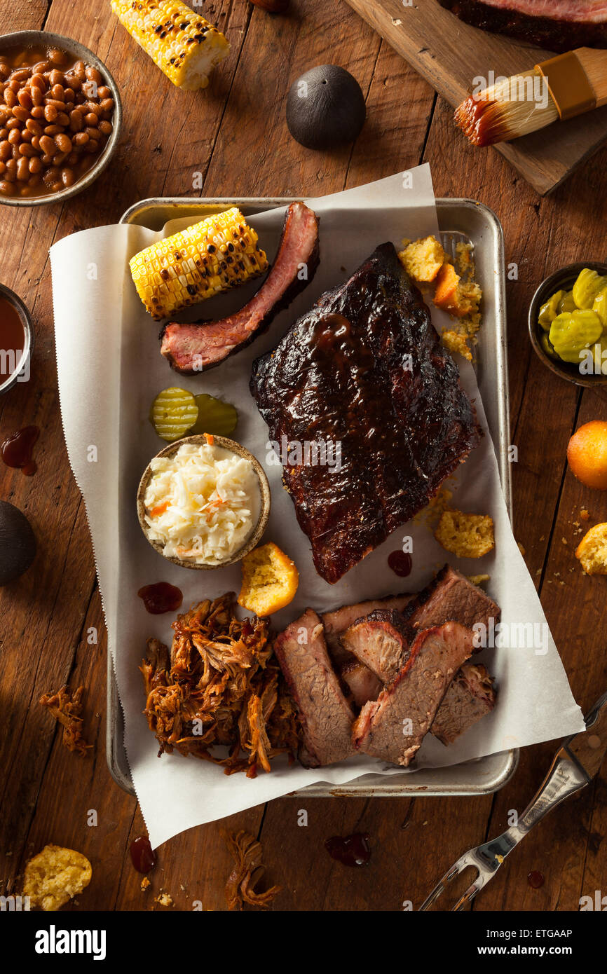 Pecho y costillas ahumadas de barbacoa con un plato de carne de cerdo y en los lados Imagen De Stock