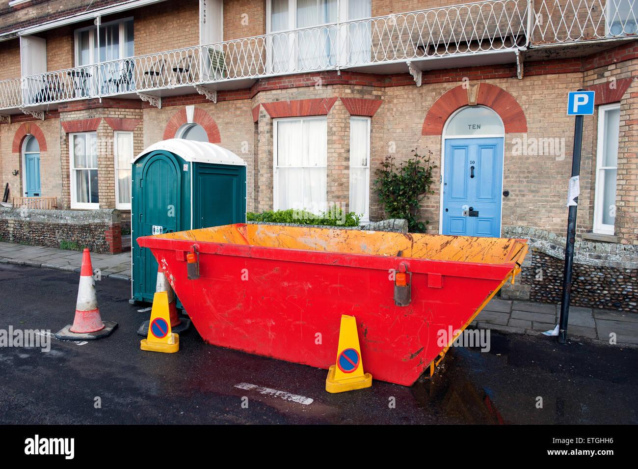 Rechazar skip y wc portátil en frente de una casa en la necesidad de renovación, de East Anglia Inglaterra Imagen De Stock