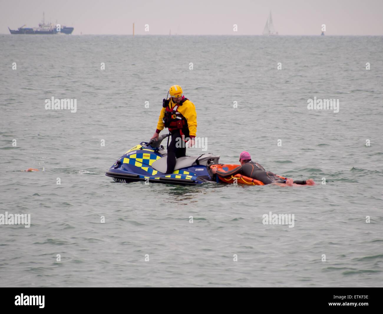 Un socorrista de una moto de agua ayuda a un nadador que está en dificultad, durante un evento en el Solent triatlón Foto de stock