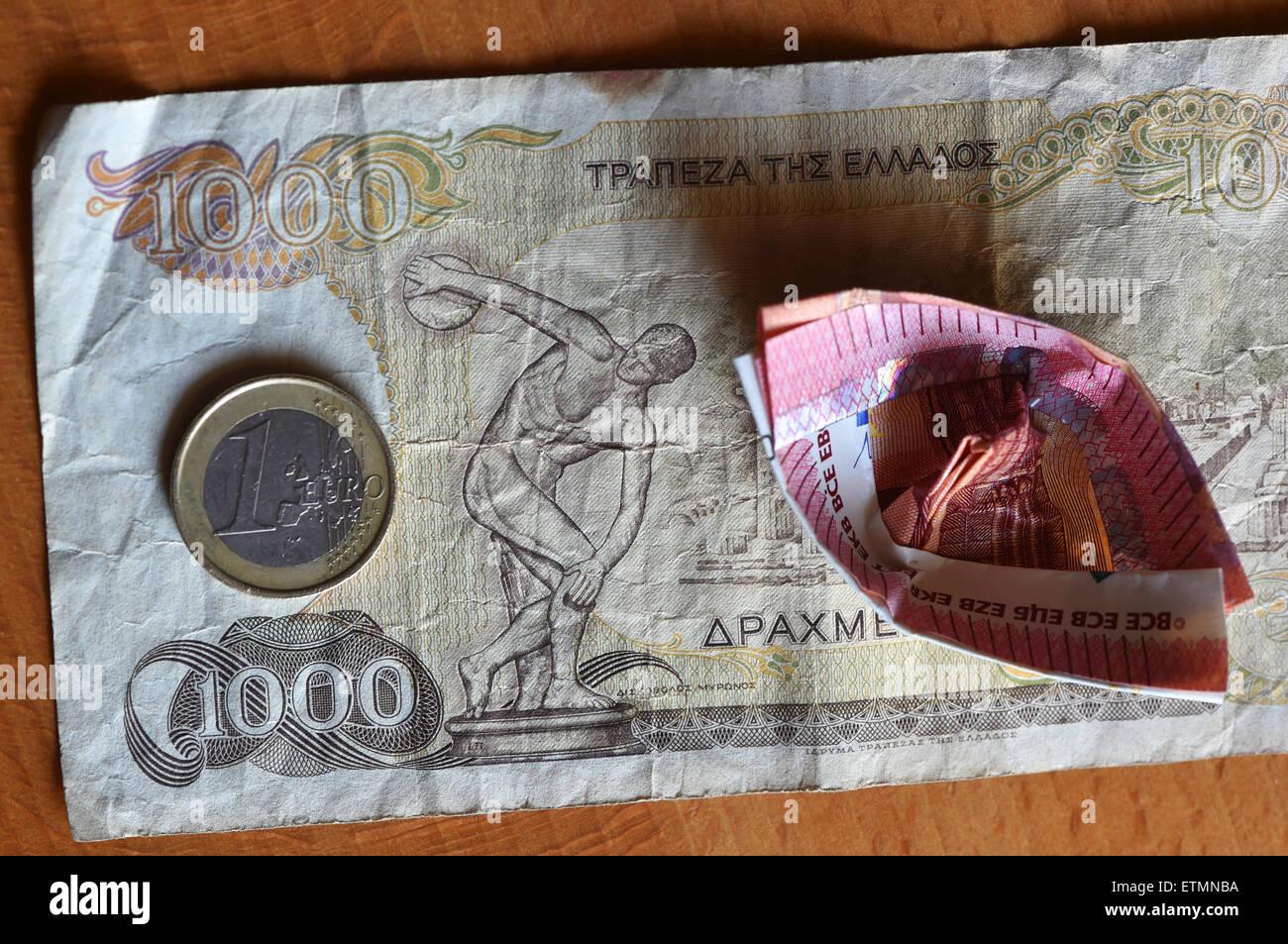 Berlín, Alemania. El 14 de junio de 2015. Ilustración - una moneda en euros y a 10 euros el proyecto de ley que ha sido doblada en un barco yace sobre un dracma griego 1000 Bill en Berlín, Alemania, el 14 de junio de 2015. Foto: Jens Kalaene/dpa/Alamy Live News Foto de stock