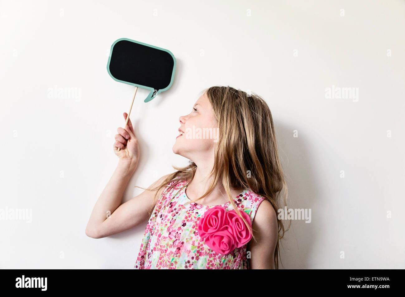 Retrato de una niña alegre celebración de un pensamiento en blanco bubble junta por encima de su cabeza Imagen De Stock