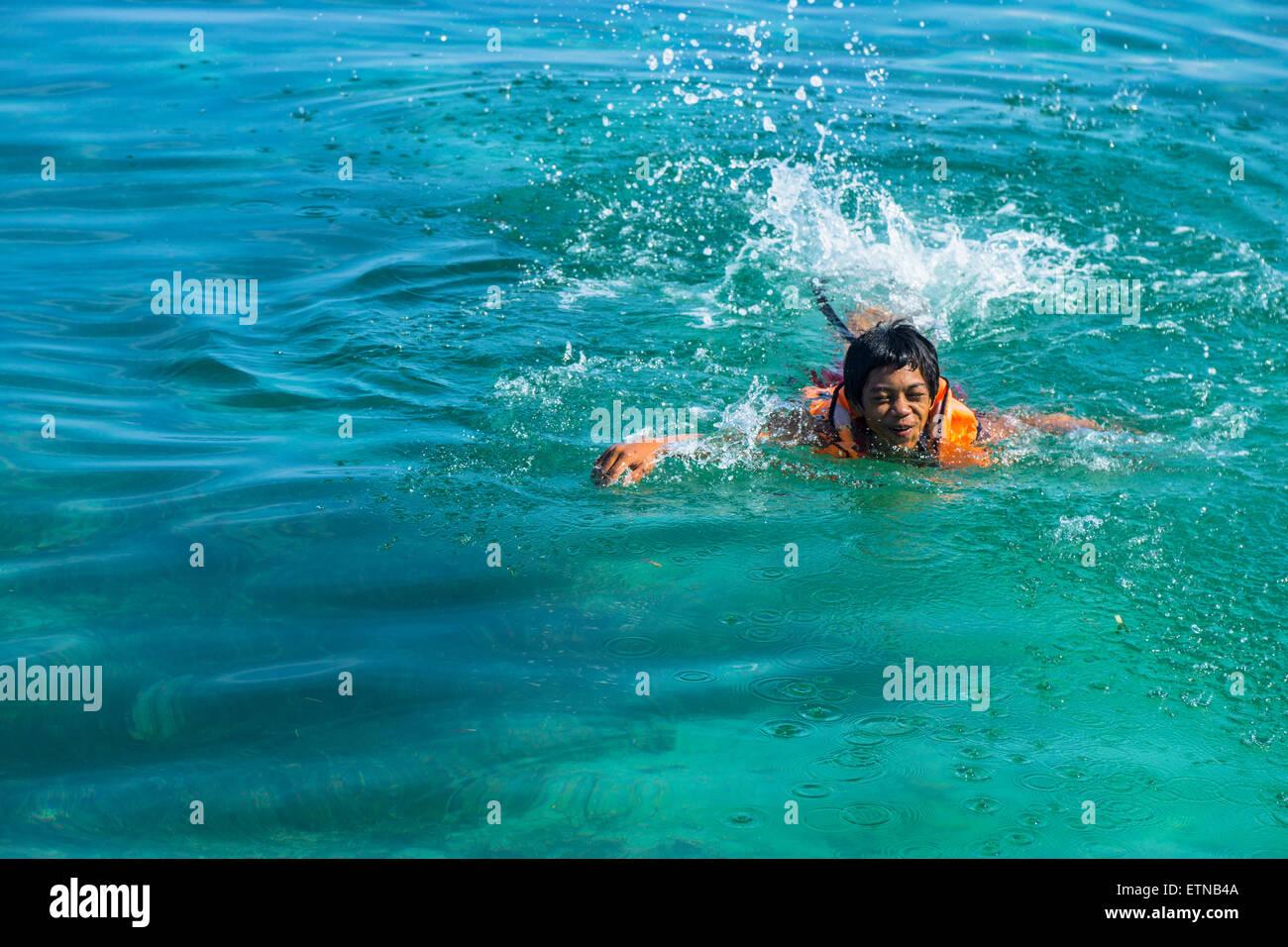 Adolescente vistiendo un chaleco salvavidas, nadando en el mar, la isla de Salakan Semporna, Sabah, Malasia Imagen De Stock
