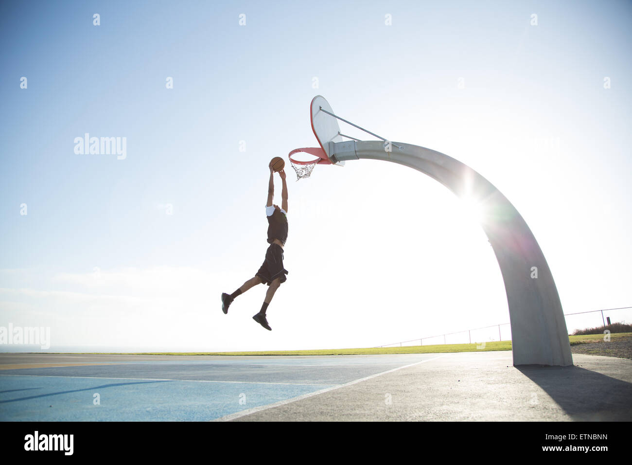 Joven jugando baloncesto en un parque, en Los Ángeles, California, Estados Unidos. Imagen De Stock